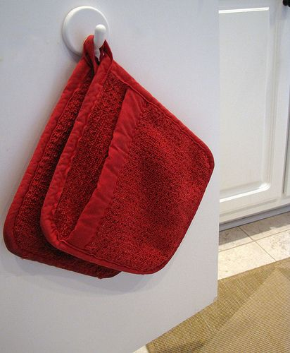 To save drawer space, hang oven mitts on a hook inside a cabinet door near your oven.