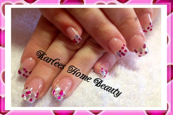 Acrylic nails with white AB glitter, pink hex glitter and silver hearts.