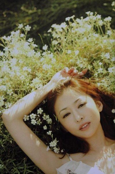 花の上に寝そべる松雪泰子