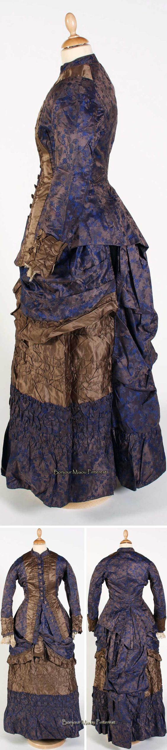 Day dress ca. 1880. Blue & gold floral brocade with bustle back. Golden brown rouged silk trim at cuffs & front of bodice, which fastens center front with long line of covered buttons. Skirt tiers in contrasting fabric; silk with a bow at center front. Bonhams
