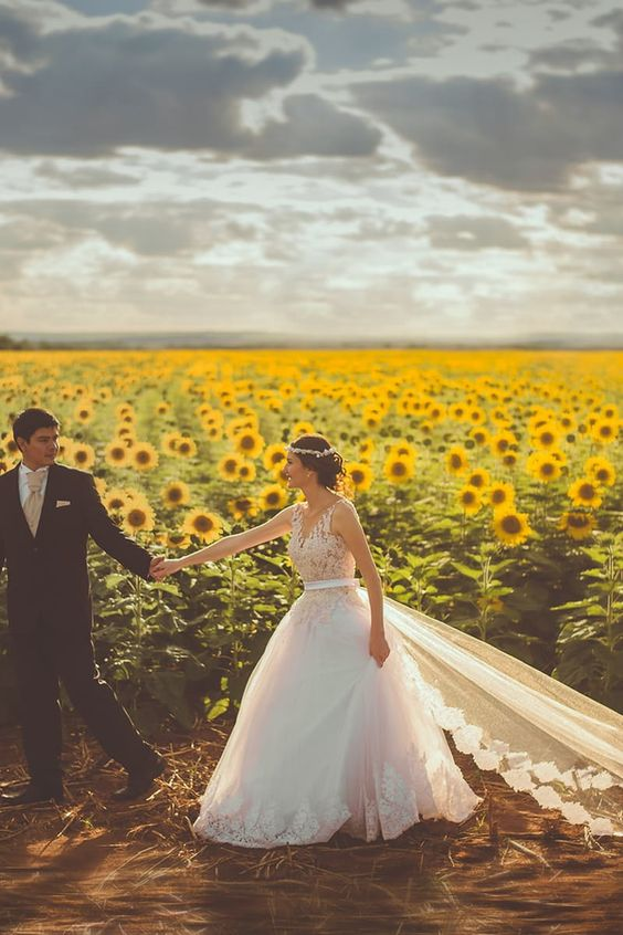 Download this free photo from Pexels at https://www.pexels.com/photo/groom-wearing-black-formal-coat-holding-bride-in-white-bridal-gown-in-yellow-and-green-sunflower-field-during-daytime-190894/ #landscape #couple #love