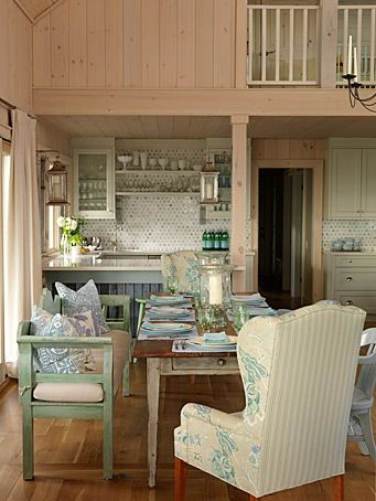 An idyllic off-the-grid lake cottage is renovated drawing inspiration from the natural surroundings and blending vintage treasures with cheerful summer hues. Mix and match chairs and bench add to the casual charm.