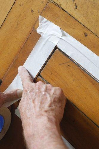 Após colar os tacos soltos, isole as bordas dos mesmos com fita crepe antes de iniciar a calafetação. Essa etapa consiste em preencher as juntas dos tacos com a massa acrílica para madeira que pode ser encontrada em lojas de material de construção e reforma. Compre-a na cor do piso. Se você desconhece a coloração do taco, leve-o na loja ou fotografe-o para mostrar ao vendedor