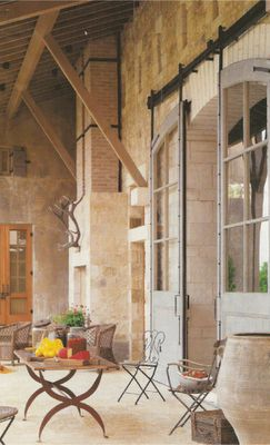 Sliding arched French doors to French country courtyard dining area. #frenchfarmhouse #europeanfarmhouse #outdoor #courtyard #dining