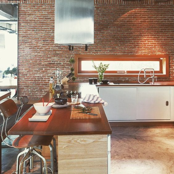 Airy loft-style kitchen with the right combination of exposed brick wall, polished concrete floor and natural wood countertops. #room #roommagazine #kitchen #loft #concrete #exposedbrick #openplankitchen #counterbar #stool #kitchendesign #loftkitchen