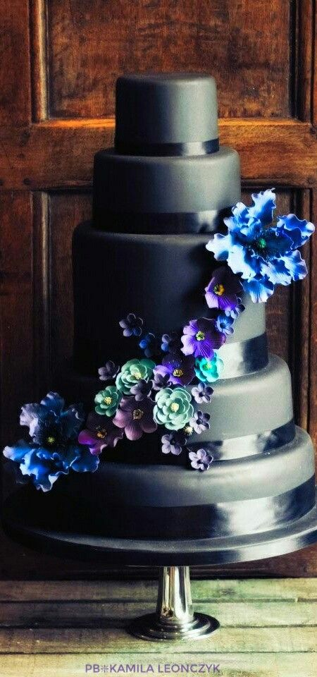 Black wedding cake with blue, purple and teal floral cascade. Different and stunning. Could also be nice for the groom if you change the flowers into some masculine accent