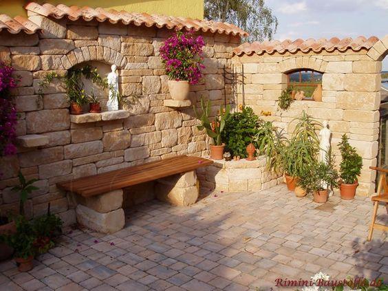 Rustikale Natursteinmauer mit Fenstern und rustikaler Sitzmöglichkeit. Als Abdeckung werden Mönch Nonne Dachziegel genommen.