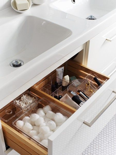 Items organized into drawers in an all white bathroom