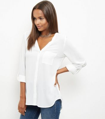 """Create a smart and sophisticated look with this white v neck 3/4 sleeve shirt- pair with jeans and ghillie heels to finish.- 3/4 sleeves- V neckline- Button front fastening- Rolled sleeves- Dip hem- Casual fit that is true to size- Model is 5'8""""/176cm and wears UK 10/EU 38/US 6"""