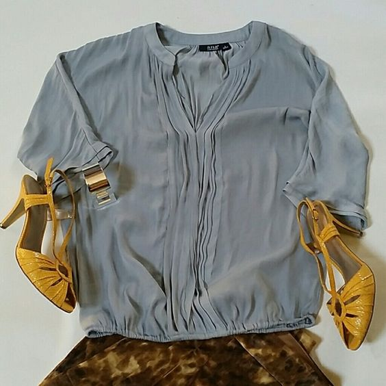 Silver grey flowing tiny ruffle blouse  a.n.a. S Very good used condition.  Color is a light silver grey.100% soft poly (not shiny or satiny). Size small. 3/4 length sleeves. Flowing top with elastic gathered waist, banded collar and v neck front. Tiny ruffles complete the look. Great dressed up with a skirt or throw on some jeans and booties and go shopping!  Very cool. I'm a medium and it just doesn't fit. Make it yours today. Bundle and save 30% or make me a reasonable offer. a.n.a Tops…