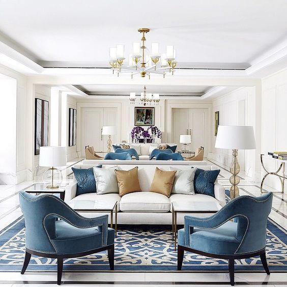 A predominantly white room with blue accent chairs, a striking blue and white rug and gold accents.