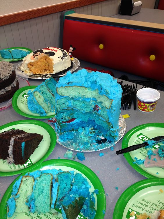 "Showed depth of the ""ocean"" with blue food coloring and used gummy fishes in the layers.  Fondant for the shark fin."