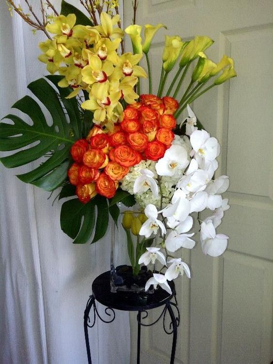 Orange roses, yellow orchids and calla Lillies with Monstera leaves and hanging #Orchids
