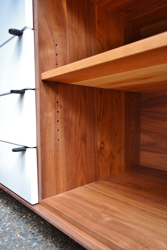 "Grid Credenza by Jeff Martin Joinery.  Solid walnut exterior, solid cherry interior, matte white door and drawer fronts, cast powdercoated pulls, dovetailed drawers, humidrawer, black powdercoated wine grid, white hollow wheel casters.  64"" L x 28"" H x 20"" W"