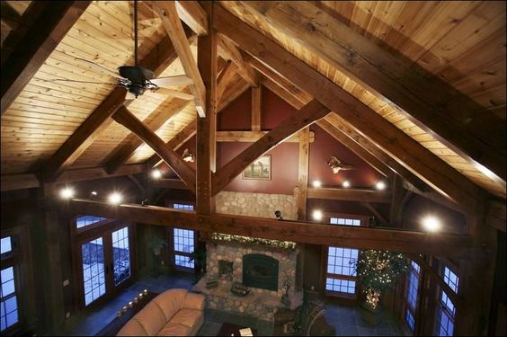 cathedral ceiling with a stone fireplace in a timber frame home