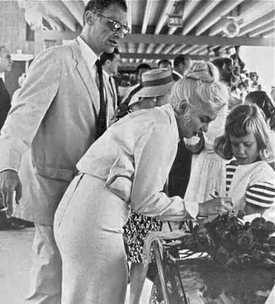 Marilyn along with Arthur Miller. signing a autograph for a little girl.