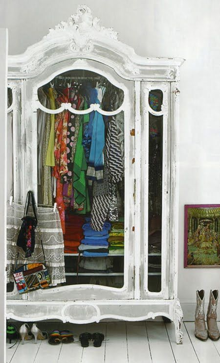 colourful clothing in a white antique cupboard