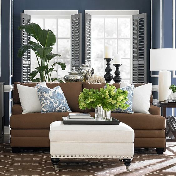 2014 Home Interior Design Trends of the Cool Blue Themed Living Room with Sweet Brown Fabric Sofa Furniture that have White Pillows and Simple Square Shaped White Table on the Classic Brown Carpet also Amazing Two Twin Window Types complete with the Fresh Green Plant in Front it