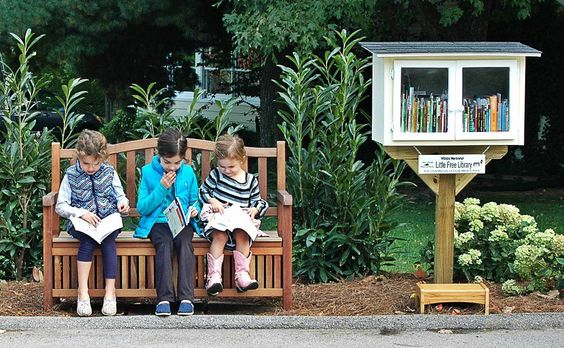 A Little Free Library on the edge of the sidewalk with a bench next to it so kids/adults can sit down and read for a spell. YES!!