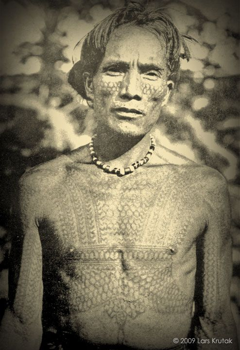 A very early 20th century photograph of a heavily tattooed Kalinga chief of Balatok village covered in python scales and centipede designs.