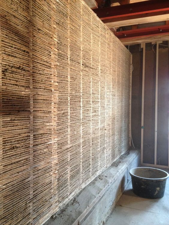 : Holzrahmenbau zur Aufnahme der Leichtlehmschüttung. Aufbringen von Reetmatten als Schüttungsbarriere. Einbringen der Lehmschüttung mit anschliessender Lehmverputzung