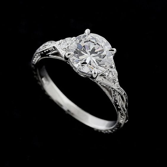 This antique style ring is made of 14k gold. Contains 7.5 mm (1.5ct) Forever One Moissanite securely set in four prongs. There are two, natural diamonds