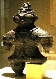 """Dogu Statue (c)wikimedia  Shakōki Dogū aus der Späten Jōmon-Zeit (1000–400 v. Chr.) und ausgestellt im Tokyo National Museum  Die Dogū (dt. """"Erdfigur"""") sind Statuen aus der traditionellen japanischen Kunst aus Terrakotta. Sie stellen meist eine weibliche Figur dar, teils aber auch Männer oder Tiere. Sie treten von der Mitte bis zum Ende der Jōmon-Zeit auf."""