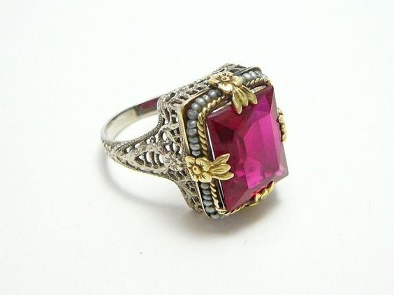 Stunning. Rare art deco ring...circa 1920.  Emerald cut ruby and imitation seed pearls on yellow gold filigree mounting.