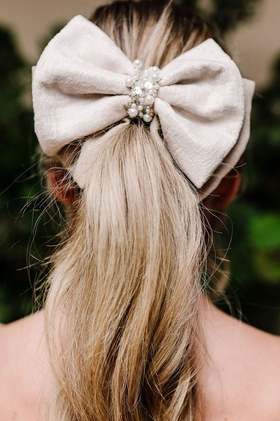 A beautiful accessory for the modern bride this luxe wedding hair bow is a chic and stylish choice. A large velvet and faux suede bridal hair bow with a wrapped pearl centre. Attach to the top of a bun or pony tail to add a gorgeous modern twist to your wedding hair. #modernbride