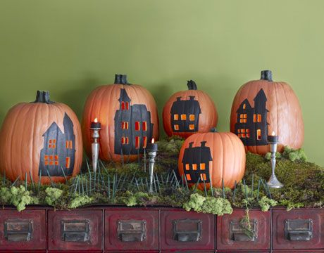 pumpkins with painted houses and lit up windows