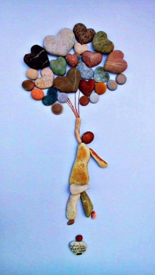 Cuadro en piedras de niño con globos. Presta atencion al detalle de las cuerdas de los globos, estan hechos con hilos.