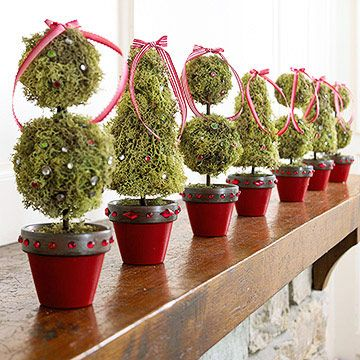 Topiaries in a Row  --  Line your mantel or windowsill with a battalion of miniature topiaries standing at attention. These mossy green plants are adorned with bows and rhinestones for a royal holiday treatment. Even the pots are decked for the holidays with adhesive rhinestones and red paint.
