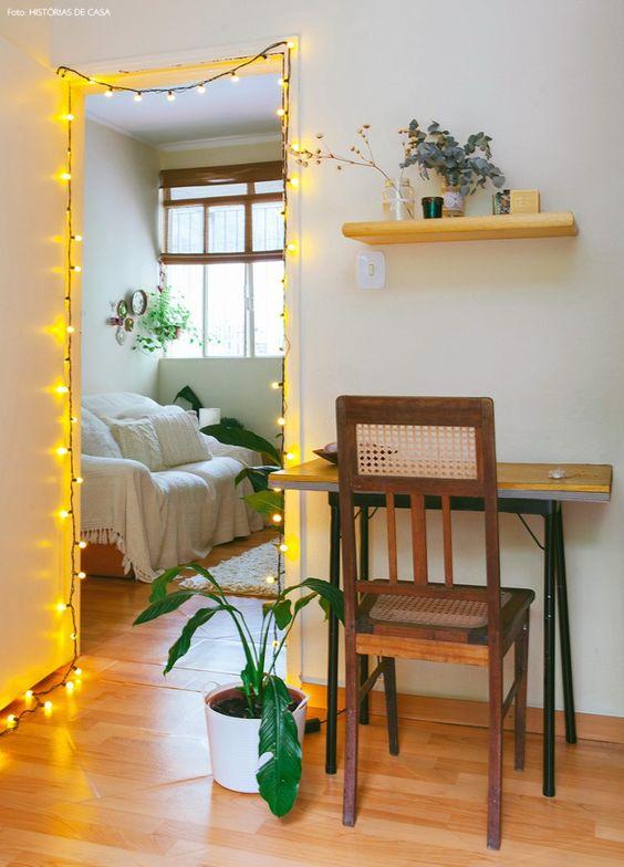 Quarto com pequena penteadeira, cadeira antiga e pisca pisca na porta.:
