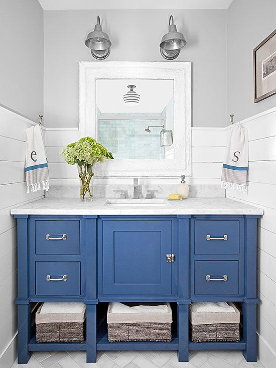Horizontal painted wood planks are an inexpensive yet eye-catching bathroom backsplash solution, and lend cottage appeal to this beautiful blue room. Keep the rustic look contemporary with industrial-style lighting and a colorful vanity.
