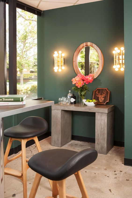 This transitional man cave features a concrete bar console, Jonathan Adler sconces and a reclaimed wood round mirror. Green walls lend a serene feel to the masculine space.
