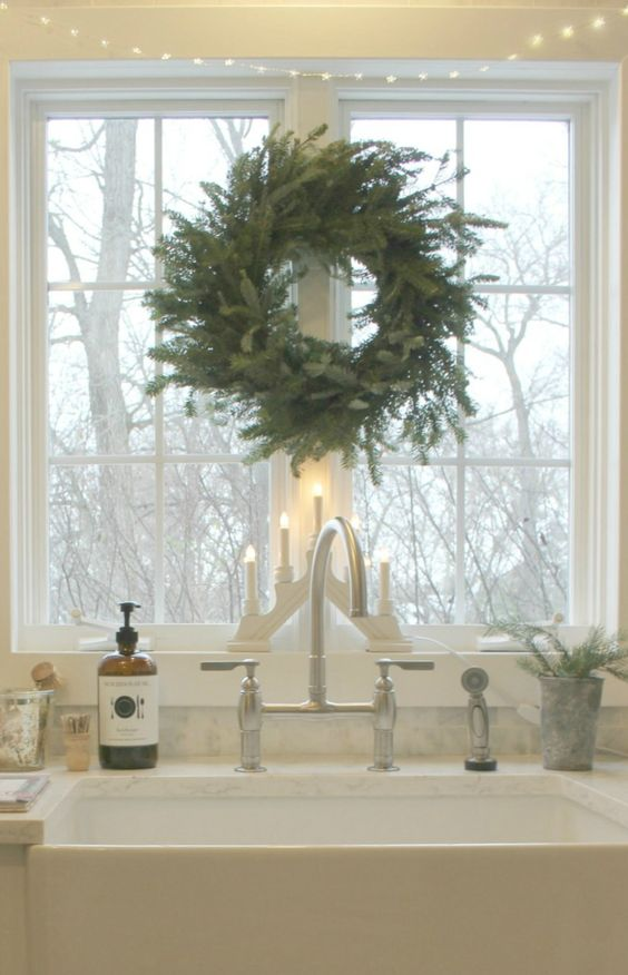 Scandinavian Christmas decor in my white kitchen with Swedish candelabra, fresh fir wreath, and fairy lights over farm sink window. #hellolovelystudio #christmasdecor #swedish #scandinavian #whitechristmas #nordicfrench