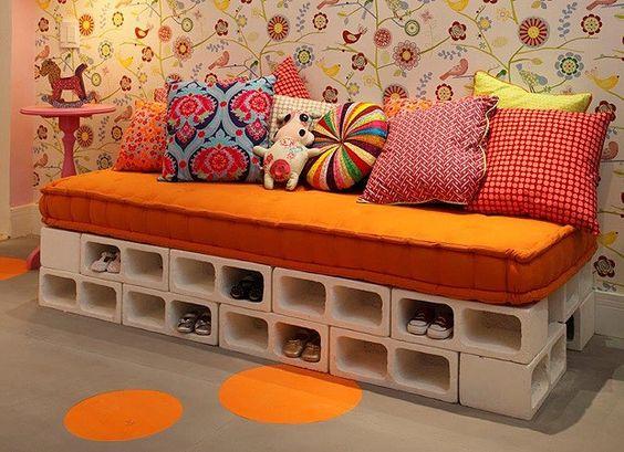 O sofá-cama foi feito com 22 blocos de concreto empilhados, ao custo de 4,20 reais cada. Sobre eles, colchão e almofadas coloridas. Os nichos ainda ser usados para guardar sapatinhos.
