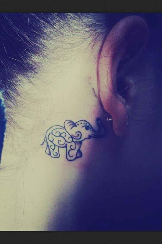Pequeño tatuaje de un elefante detrás de la oreja.