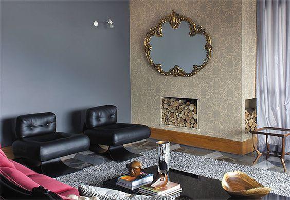 Sala decorada pelo designer Marcelo Rosenbaum, com papel de parede adamascado dourado em torno da lareira. A parede abriga um belo espelho com moldura antiga. As poltronas de couro preto são assinadas por Oscar Niemeyer