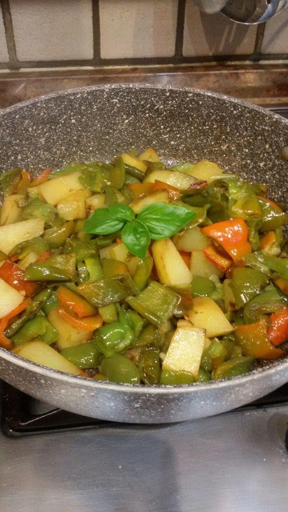 Patate e peperoni in padella by Laura  mettete una padella con un po di olio sul fuoco, quando l'olio è  caldo aggiungere i peperoni e le patate a pezzetti, cuocere a fuoco abbastanza alto fino a doratura,  poi coprire con coperchio fino a cottura. Salate e aggiungete foglie di basilico