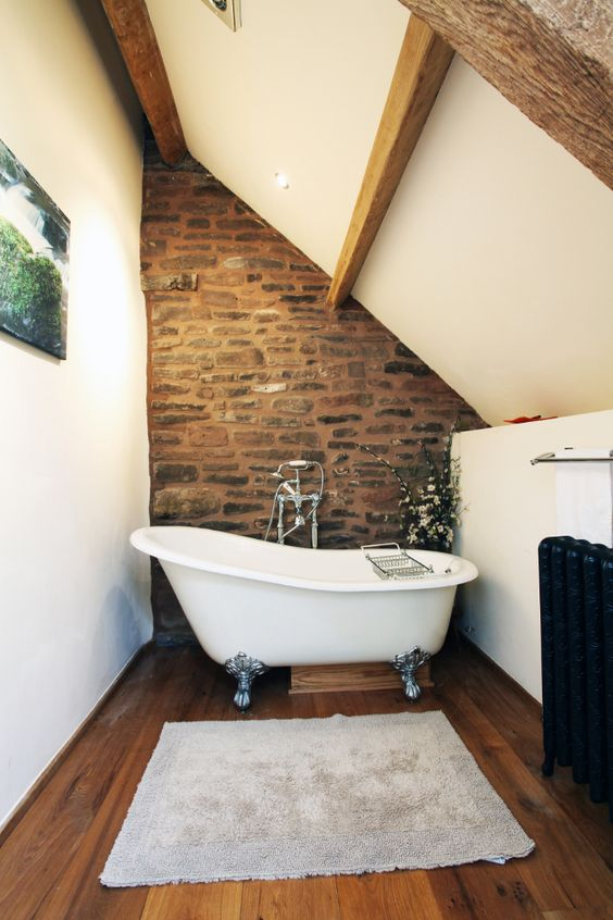 Attic bathrom with solid oak flooring, medieval oak A frames, toilet, large washbasin, illuminated vanity mirror and a traditional cast iron roll top bath.