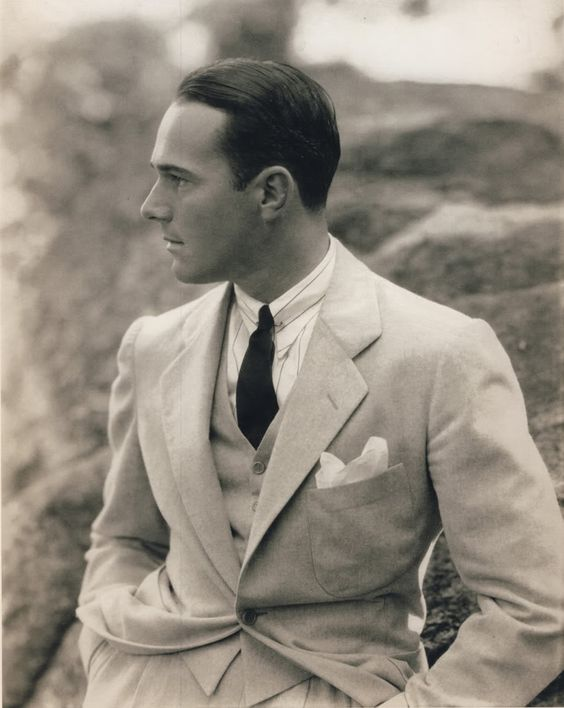 Actor William Haines, 1930.  Note how much narrower shoulders are here than even just three years later, and one button jacket!   Super pointed collar is trendy -- note the pin holding the collar together just under the small tie know