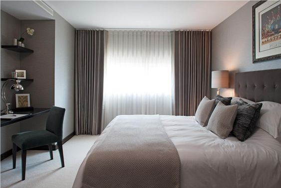 Hotel style bedroom chic... I like the idea of the curtains on the entire wall, not just the windows.