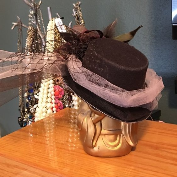 """Mini Top Hat Fascinator - Dk Brown Steampunk Style This is a mini top hat fascinator. Dark brown heavily embellished with feathers, ribbon, Crystal's, beads, bird cage & tulle. Worn once. Very steampunk. Brim measures 5.5"""" front to back 5"""" side to side. 2"""" in height. Accessories Hats"""