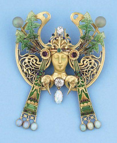 Broche - pendentif en or jaune, émail et émail plique à jour représentant une tête de femme ornée de diamants, d'émeraudes, d'opales, d'améthystes et péridots. Travail de Paul Briançon - Ancien chef d'atelier de R. LALIQUE. Vers 1900. (Petit éclat à l'émail). P. 45,2g