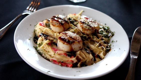... Scallops served with angel hair pasta, roasted red peppers, and