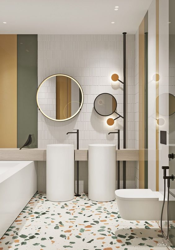 The family bathroom that the kids frequent has striped yellow, green and white decor, with a matching terrazzo floor. Two bathroom sinks reduce sibling squabbles over wash space in the mornings.