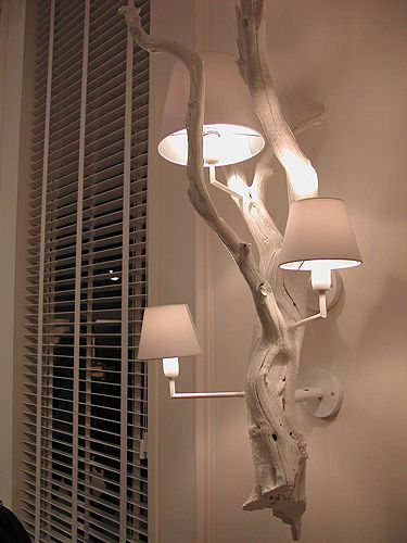 driftwood lamp installed in a wall - since it's all painted white it has a rustic-meets-modern feel