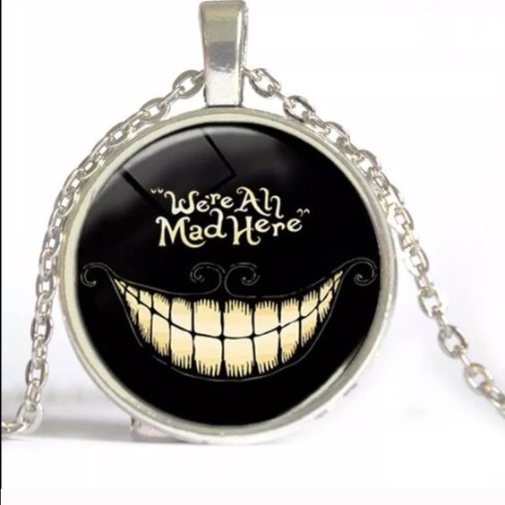 WE'RE ALL MAD HERE Silver tone about 20 inches long. Medallion is about an inch. Jewelry Necklaces