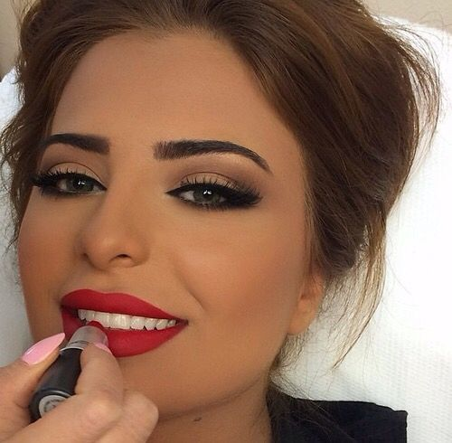Browns and nude eyeshadow shades with a red lip as the focal point for a balanced look.